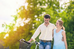 Human Relationships. Happy Couple Outdoors Walking with Bike. Stock Images