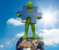Human representation standing on earth. And holding a jigsaw piece Royalty Free Stock Photos
