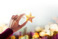 Human Resource Management or Talent Concept, Hand holding and Ra. Ise up a Golden Star, Blured Bokeh Light as background royalty free stock image