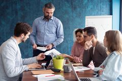 Human resource manager training people about company and future prospects. Group of businesspeople sitting in meeting. Room and listening to the speaker. Leader stock photo
