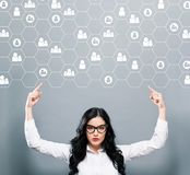 Human Resources concept with business woman pointing upwards. On a gray background Royalty Free Stock Photos