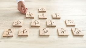 Human resources concept with a businessman arranging a series of. Wooden blocks depicting people into a pyramid Stock Image