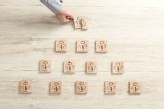 Human resources concept with pyramid of figures on wooden blocks. Pyramid of figures on wooden blocks with the hand of a businessman reaching out to place one of Royalty Free Stock Image
