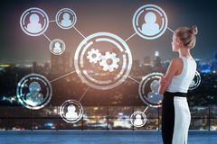 Human resources concept. Thoughtful young businesswoman standing on rooftop with connected people and cogwheel icons on night city background. Human resources Royalty Free Stock Images