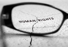 Human rights. Humen rights text through reading glasses royalty free stock images