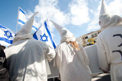 Human Rights March in Tel Aviv. TEL AVIV - NOVEMBER 9: Israeli activists dress as KKK members to satirize right-wing Israeli policies and politicians during in Royalty Free Stock Photo