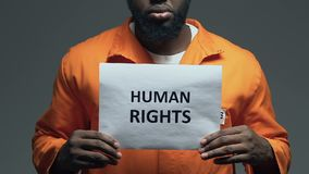 Human rights phrase on cardboard in hands of African-American prisoner, assault. Stock footage stock footage
