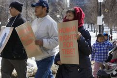 Human Rights For Tibet. Boston, Massachusetts USA - March 2013 - Couple holding signs Human Rights For Tibet during the Boston Free Tibet march through the Royalty Free Stock Photo
