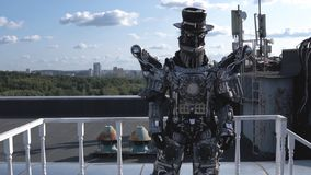 Human robot in all growth is driven by limbs on background of blue sky with clouds. Footage. Android with face and hat. Demonstrates its ability to move stock image