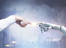 Human and robot hands reaching out, blue city. Human and robot hands reaching out and touching with index fingers. A blue cityscape background. Toned image royalty free stock photos