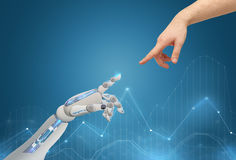 Human and robot hands reaching to each other. Science, future technology and progress concept - human and robot hands reaching to each other Stock Photo