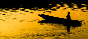 Human rowing on the boat over dramatic sunset Royalty Free Stock Photo