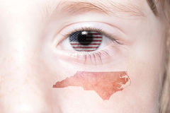 Human`s face with national flag of united states of america and north carolina state map. Concept stock photos