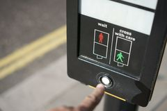 Humans finger presses the traffic lights button. Human`s finger presses the traffic lights button to cross the road to the green light Stock Photos