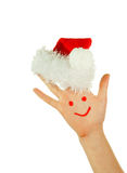Human's palm with smile on and Santa's hat Stock Photo