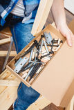 Human with screwdriver and nails. DIY. Stock Photo