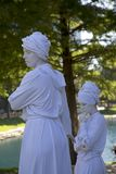 Human sculptures wearing turbans profile. Two white female human sculpture wearing turbans in the park .It is show on Frisco Annual Arts Walk , TX USA 2017 Royalty Free Stock Photos