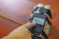 Human setting the timer on a cellphone connected to explosives Stock Images