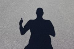 Human shadow on gray concrete ground giving the thumbs-up sign with one hand stock image