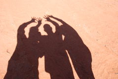 Human Shadows on Red Clay Sand. Three people working together as a team with hands in the air, fingers outstretched, shadow over red clay sand Royalty Free Stock Photos