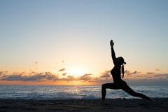 Human silhouette doing yoga on the beach in front of rising sun royalty free stock images