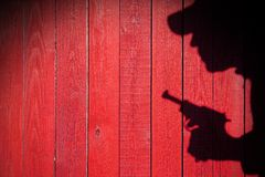 Human silhouette with handgun in shadow on wood background, XXXL Royalty Free Stock Images