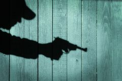 Human silhouette with handgun in shadow on wood background, XXXL Stock Photos
