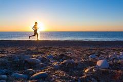 Human Silhouette jogging along Ocean Beach at Sunrise Royalty Free Stock Photos