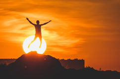 Human silhouette jumping at solar disk sunny summer sunset drive holidays and vacations Stock Images