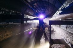 Human silhouette with led headlight in underground communication. Heating main, sewer tunnel, etc stock photos