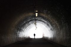 Human Silhouette in Light at The End of The Tunnel Stock Photo