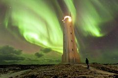 Human silhouette and lighthouse in Iceland under impresive aurora borealis spectacle. Lightouse in Iceland shoreline under magnetic storm spectacle. Human looks royalty free stock photo