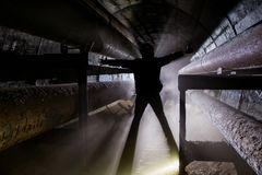 Human silhouette with in underground communication, heating main, sewer tunnel, etc.  royalty free stock photo
