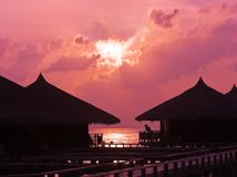 Human silhouette in water bungalow at sunset Royalty Free Stock Photography