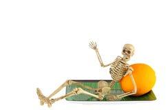 Human skeleton leaning on orange, relaxing Stock Image