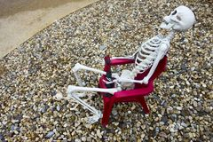 Human Skeleton Model sitting in Red Chair Halloween Decoration stock image
