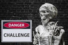 Human skeleton and sign danger challange stock image