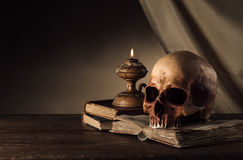 Human skull and ancient books still life. Human skull, lit candle and open ancient book on an old wooden table, knowledge and literacy concept Stock Images
