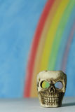 Human skull with a blue sky and rainbow background Royalty Free Stock Images