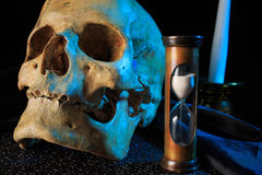 Human skull on a book next to the clock. concept Stock Photography