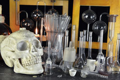 Human skull with bottles on alchemy table. Scary skull with vintage bottles and esoteric glassware in alchemy laboratory. Halloween, old pharmacy or historical royalty free stock photos