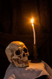 Human skull and burning candle Stock Images