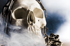 Human skull with chain and smoke Stock Photography