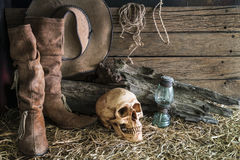 Human skull and cowboy boots in barn background. Still life with human skull on hay with traditional leather boots and american west rodeo brown cowboy hat stock images
