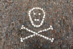 Human skull and crossbones depicted on pavement. Stock Photos