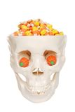 Human skull filled with candy corn and pumpkin eye Stock Photo