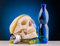 Human skull and fitness dumbbells and bottle of water Royalty Free Stock Photo