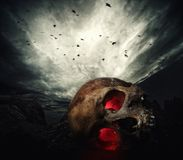 Human skull with glowing eyes. Against stormy sky royalty free stock photos