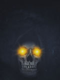 Human skull in hood with burning eyes on dark background. Hallow. Een grunge banner Stock Photography