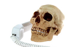Human skull model with old telephone Royalty Free Stock Photography
